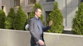 Молодой бизнесмен идя вниз по улице и счастливо связывает на видео- звонке