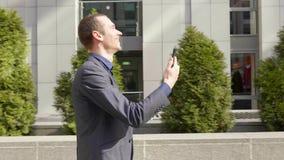 Молодой бизнесмен идя вниз по улице и счастливо связывает на видео- звонке видеоматериал