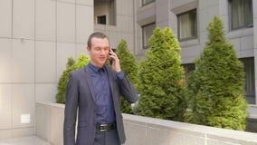Молодой бизнесмен идя вниз по улице и счастливо связывает на телефонном звонке