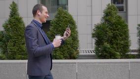 Молодой бизнесмен идя вниз по улице с беспроводными наушниками в ушах и счастливо связывает на видео- звонке видеоматериал