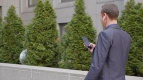 Молодой бизнесмен идя вниз по улице с беспроводными наушниками и написать сообщение на смартфоне