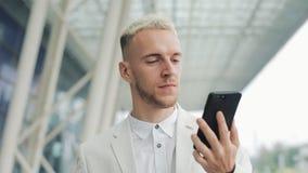 Молодой бизнесмен идя в город около аэропорта и записывая сообщение голоса на смартфоне дело успешное сток-видео