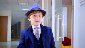 Молодой бизнесмен идя на коридор в офисе Серьезный молодой мальчик в деловом костюме и шляпе идя на школу видеоматериал