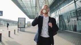 Молодой бизнесмен идя около офисного здания и выпивая кофе Красивый парень наслаждается кофе утра для того чтобы пойти замедленно видеоматериал