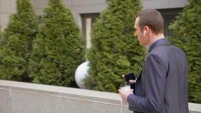 Молодой бизнесмен идя с беспроводными наушниками и агрессивно водит обсуждение на телефонном звонке