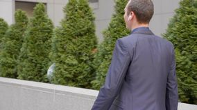 Молодой бизнесмен идя с беспроводными наушниками и счастливо связывает на телефонном звонке