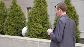 Молодой бизнесмен идя с беспроводными наушниками и счастливо связывает на телефонном звонке видеоматериал