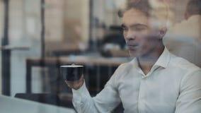 Молодой бизнесмен используя ноутбук на уютной кофейне и выпивающ кофе акции видеоматериалы