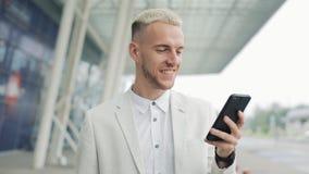 Молодой бизнесмен используя приложение дела на смартфоне идя в городе около аэропорта детеныши бизнесмена красивые акции видеоматериалы