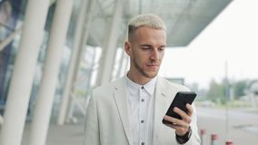 Молодой бизнесмен используя приложение дела на смартфоне идя в городе около аэропорта детеныши бизнесмена красивые сток-видео