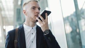 Молодой бизнесмен используя приложение дела на смартфоне идя в городе около аэропорта Он отправляет сообщение голоса Красивые дет акции видеоматериалы