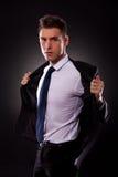 Молодой бизнесмен кладя вне его куртку стоковые изображения rf