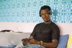 Молодой бизнесмен красивого и счастливого хипстера черный Афро-американский работая с усмехаться ноутбука и наушников удовлетворе стоковые изображения rf