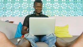 Молодой бизнесмен красивого и счастливого хипстера черный Афро-американский работая с усмехаться ноутбука и наушников удовлетворе стоковая фотография rf