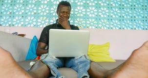 Молодой бизнесмен красивой и счастливой черноты хипстера афро американский работая с усмехаться ноутбука и наушников удовлетворен стоковая фотография