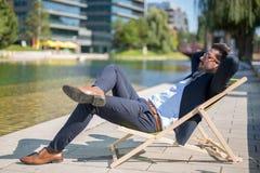 Молодой бизнесмен наслаждаясь его перерывом на sunbed перед офисом стоковые фото
