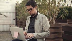 Молодой бизнесмен начиная startup проект на компьтер-книжке сидя на стенде акции видеоматериалы