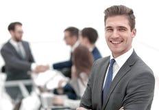 Молодой бизнесмен на запачканной предпосылке офиса стоковые фото