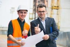 Молодой бизнесмен на строительном бизнесе планирует сделать их работу эффективный Средний палец обеих выставок стоковая фотография rf