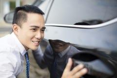 молодой бизнесмен обнимая новый автомобиль стоковое изображение
