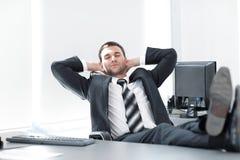 Молодой бизнесмен ослабляет сидеть на его столе Стоковое Изображение