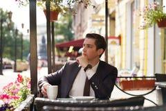 Молодой бизнесмен пришел пообедать в кафе, он сидит на таблице и ждет кто-то стоковое фото