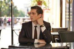 Молодой бизнесмен пришел пообедать в кафе, он сидит на таблице и ждет кто-то стоковая фотография rf