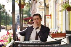Молодой бизнесмен пришел пообедать в кафе, он сидит на таблице и ждет кто-то стоковые изображения rf