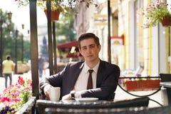 Молодой бизнесмен пришел пообедать в кафе, он сидит на таблице и ждет кто-то стоковые фотографии rf