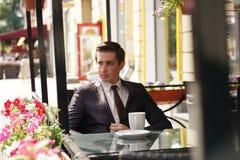 Молодой бизнесмен пришел пообедать в кафе, он сидит на таблице и ждет кто-то стоковая фотография