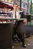 Молодой бизнесмен пришел пообедать в кафе, он сидит на таблице и ждет кто-то стоковые изображения