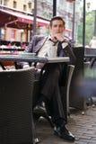 Молодой бизнесмен пришел пообедать в кафе, он сидит на таблице и ждет кто-то стоковое изображение rf
