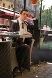 Молодой бизнесмен пришел пообедать в кафе, он сидит на таблице и ждет кто-то стоковое изображение