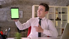 Молодой бизнесмен работает с таблеткой в офисе, показывая зеленый экран, пункт на ем, концепция дела, сообщение сток-видео