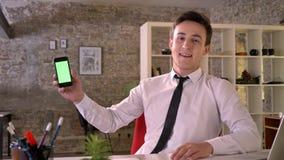 Молодой бизнесмен работает с smartphone в офисе, показывая зеленый экран, пункт на ем, концепция дела сток-видео