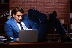 Молодой бизнесмен работая в офисе вечером стоковое фото