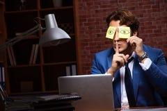 Молодой бизнесмен работая в офисе вечером стоковые фото