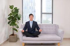 Молодой бизнесмен размышляя на софе в офисе стоковое фото rf