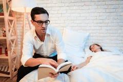 Молодой бизнесмен сидит на кровати рядом с молодой женщиной и читает книгу Женщина уснувшая стоковое изображение rf