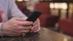 Молодой бизнесмен сидя на таблице в кафе используя iphone и отправляя SMS печатающ сообщение - успешные людей, ежедневно акции видеоматериалы