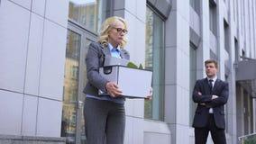 Молодой бизнесмен смотря уволенную достигшую возраста даму покидая офис, конкуренция сток-видео