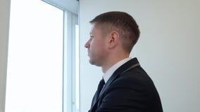Молодой бизнесмен смотря через окно видеоматериал