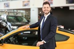 Молодой бизнесмен стоя около автомобиля в салоне стоковая фотография rf