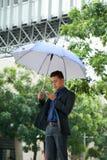 Молодой бизнесмен стоя с зонтиком в улице Стоковое фото RF