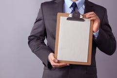 Молодой бизнесмен стоя с папкой, на серой предпосылке стоковые фотографии rf