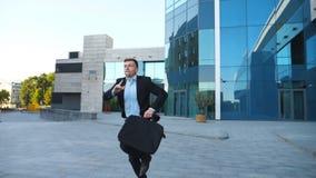 Молодой бизнесмен с бегами и взглядами портфеля на его дозоре Уверенный парень последний для встречи Успешный человек в костюме сток-видео