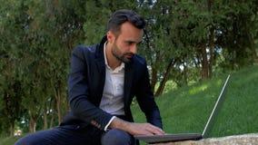Молодой бизнесмен с бородой сидит в парке на предпосылке травы и деревьев и работах на ноутбуке человек печатает на a акции видеоматериалы