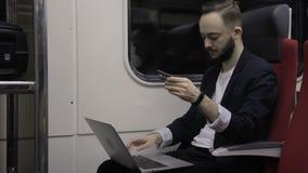 Молодой бизнесмен с компьтер-книжкой и кредитной карточкой сидит в поезде видеоматериал