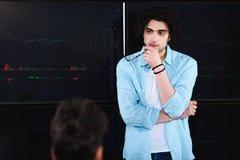 молодой бизнесмен с eyeglasses в руке стоя перед доской с графиками на современном стоковое фото rf