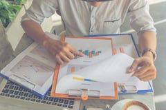Молодой бизнесмен читая финансовый номер на отчете стоковая фотография rf